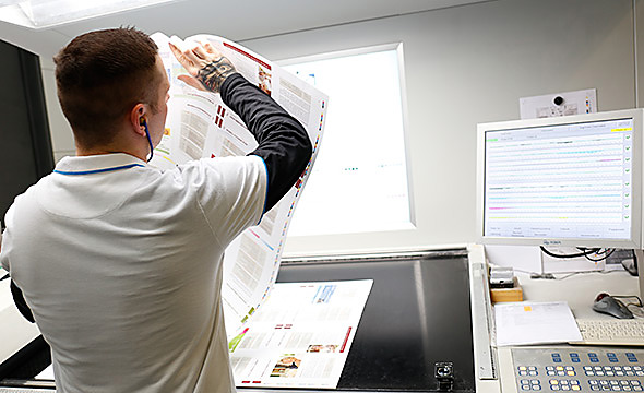 A staff member performing a final artwork check on a press sheet